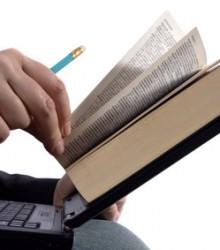 Mann arbeitet an Laptop mit Buch